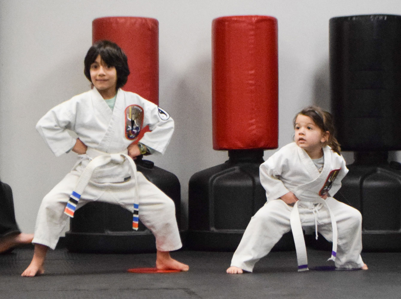 2 Little GEMs in a stance in front of kick bags