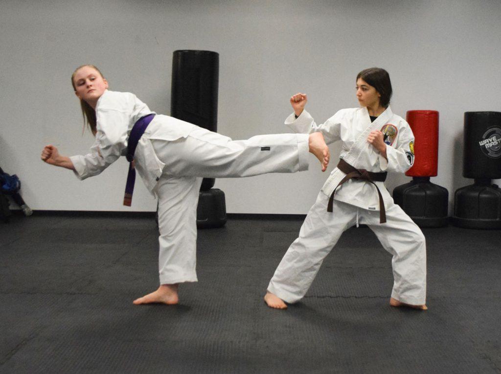 Two Teen Girls practicing kicks